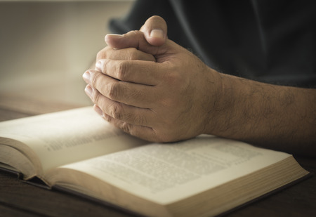 Hands of a man in prayer on a Holy Bible . religion concept