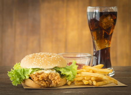classic burger: fast food set hamburger and french fries with cola on wood background.
