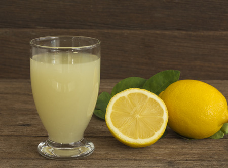 Fresh lemon juice in a glass placed on a wooden floor.