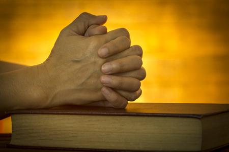 biblia: La mano del hombre colocado en la Biblia, orar a Dios. Foto de archivo