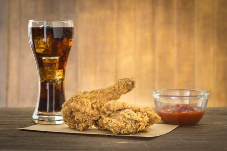 Fried chicken and cola drinks on a wooden table.