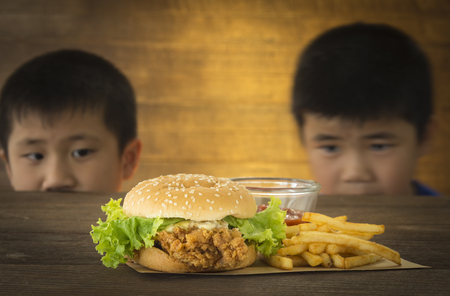 Two hungry children stared want to eat a burger on a wooden table.