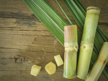 Fresh sugarcane cut into pieces on a wooden table with leaves and cane.