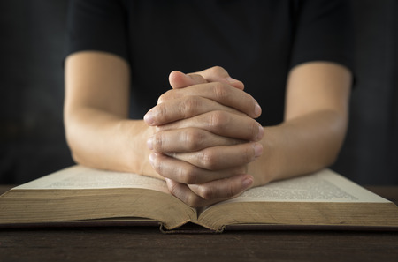 Hands of a human in prayer on a Holy Bible . religion concept.