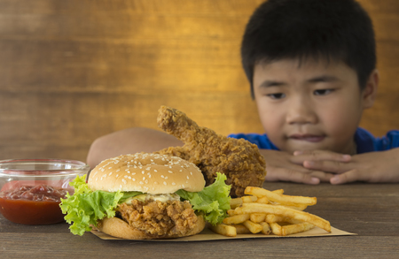 배고픈 아이들은 나무 테이블에 햄버거를 먹고 싶어 보았다.