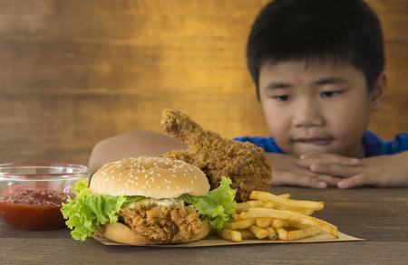 głodnych dzieci patrzył chcesz zjeść hamburgera na drewnianym stole. Zdjęcie Seryjne