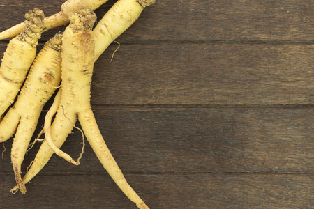 Ginseng root is placed on the wooden floor; Herbal Health Care.