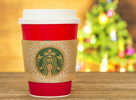 cup: Bangkok, Thailand - November 5, 2015: The new paper cup of Starbucks stores in the country for the Christmas on a red background cup. Starbucks brand is one of the world famous from USA.