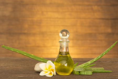 top veiw: aloe vera  oil on wooden table with light orange background.