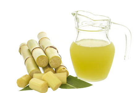 treacle: Fresh squeezed sugar cane juice in jug with cut pieces cane isolated on white background Stock Photo