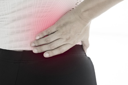 back sprains: Back view of a young women waist ache  (muscle pain). Red around the pain area. Stock Photo
