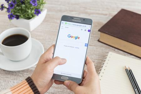 BANKKOK, タイ - 2 月 11,2016: スマート フォン ノート 5 を使用して人間の手は、Google 検索を表示します。 報道画像