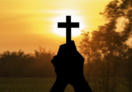 bible altar: silhouette human hands holding a cross holy and prayed for blessings from God on blur background of the sunset.