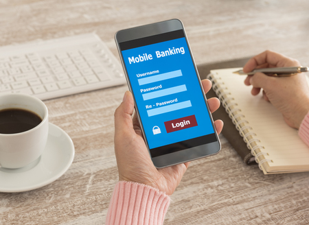 Human holding mobile smart phone with mobile banking application.