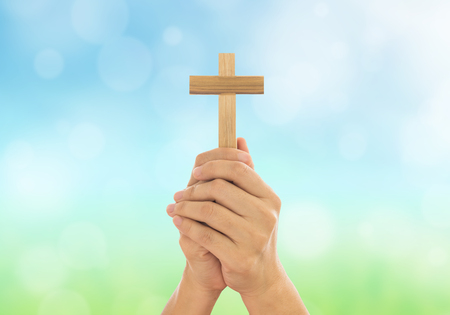 Human hands holding a cross holy and prayed for blessings from God. Amour Worship God concept.