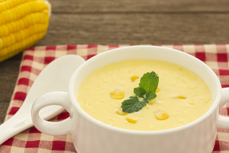 Closeup, Cream corn soup on a wooden table.