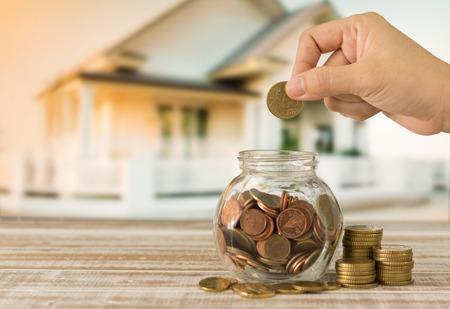 손으로 여자 돈을 단지에 황금 동전을 퍼 팅. 부동산 투자의 개념, 주택 보험, 주택 저축 계획.