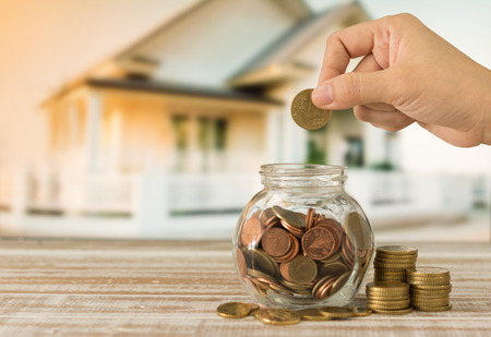 Hand's women putting golden coins in money jar. Concept of real estate investments, Home insurance, Savings plans for housing.