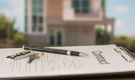 closeup pen on contract document with house key in house background.