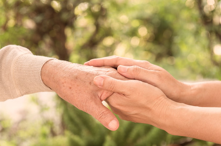 Comforting hand. Concpet of care for the elderly at home.