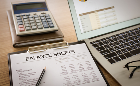 close-up balance sheet report of company's financial statement on investor's desk.
