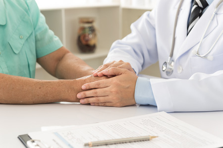 reassuring: Hand of doctor reassuring him female patient. helping hand concept. medical concept. Stock Photo