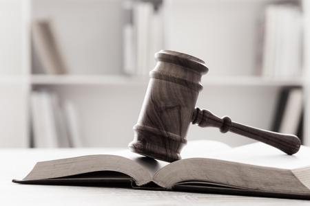 クローズ アップ木製裁判官小槌法的本の木製のテーブルの上。 ソフト フォーカス。