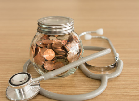 Coin jar,stethoscope on desk. concept of retirement planning , personal financial planning, health insurance. Stock Photo