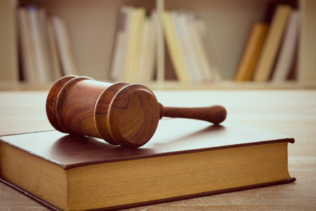 wooden judges gavel resting on top of the legal books. soft focus.