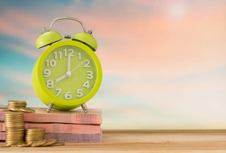 clock with money on desk in nature background.  concept of time is money, save time, Investment term.