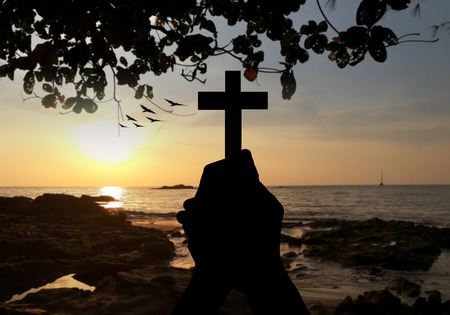 blessings: silhouette human hands holding a cross holy and prayed for blessings from God whit blur the background of the sunset.  Amour Worship God concept. Stock Photo