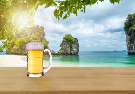 Beer is placed on a wooden table and view of tropical blurred beach background. For product display. - beach and summer concepts. Stock Photo