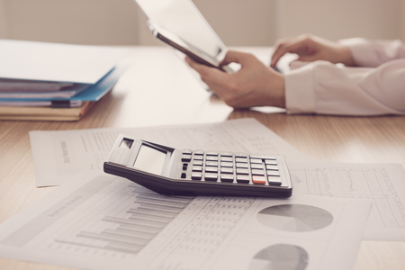 Closeup calculator on business and financial report with business people are analyzing growth business. Accounting concept. vintage style. Stock Photo