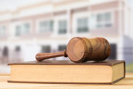 building regulations: Gavel, law books with building in background. Construction law concept. Stock Photo