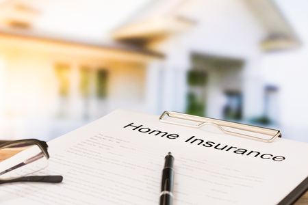 insurer: Insurance policy and a pen with home in background. Home insurance concepts.