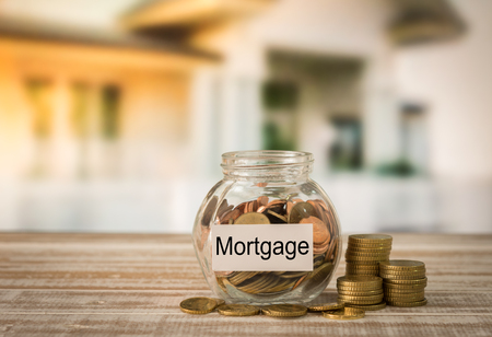 Golden coins in money jar with mortgage label. Concept of financial planning for housing, home savings, home loans. Stock Photo