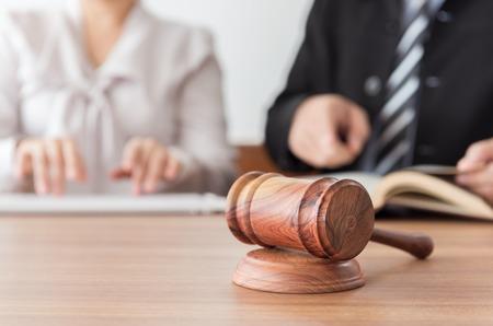Rechtershamer met advocaten die teamvergadering hebben bij wetsfirma op achtergrond. Concepten van recht, juridisch advies en diensten, online veiling. Stockfoto