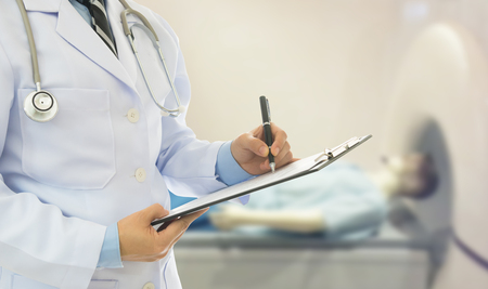 Doctor holding clipboard and take notes the treatment effect with an surgery room at the background. surgeon and medical concept.