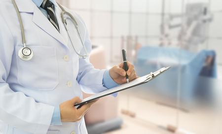 Doctor sosteniendo el portapapeles y tomar notas el efecto del tratamiento con una sala de cirugía en el fondo. Cirujano y concepto médico.