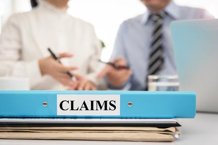 회의실의 청구서 폴더, 변호사가 보험금 청구 정책을 위해 이사 진과 이야기합니다.