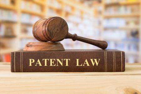 特許法の本裁判官小槌を持ったライブラリ内の机の上。法学教育のコンセプトです。