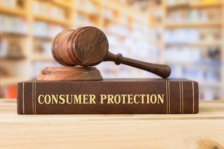 Libros de ley sobre la protección del consumidor y un martillo sobre el escritorio en la biblioteca. Concepto de educación jurídica.