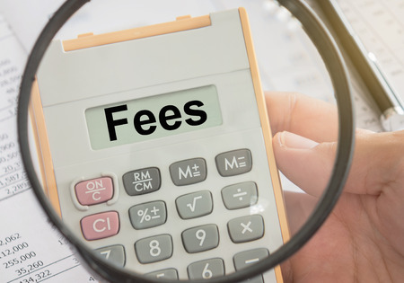 fees text displayed on calculator and magnifier. bank fees, service fee concept.