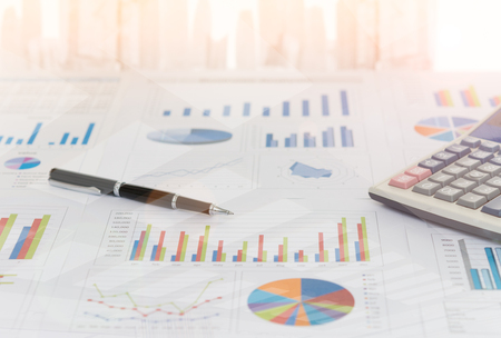 Pen on earnings report with calculator on desk of financial adviser. Concept of invest planning, analyze return on investment. Stock Photo