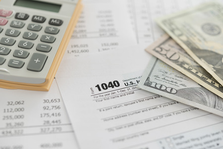 U.S. Individual Income Tax Return - 1040 tax form and calculator, money for calculation and audit tax return.