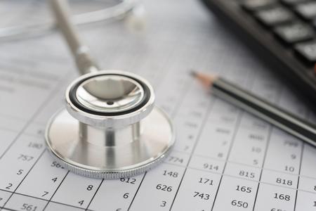 medische facturering, stethoscoop en rekenmachine op rekeningen voor ziektekosten of medische verzekering. Stockfoto