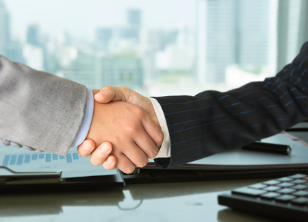 Business partners shaking hands congratulations after success to mergers and acquisitions.