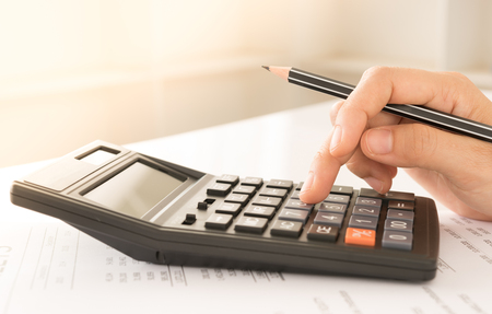 Accountant or Banker using a calculator to calculate the numbers. Concept of Savings, Finances and Accounting.