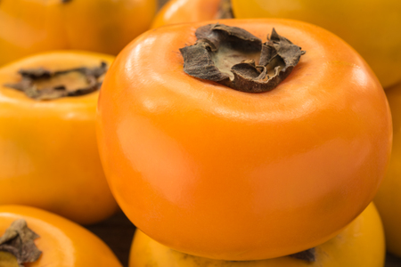 Ripe Persimmon sweet summer fruit on wooden background. Stock Photo