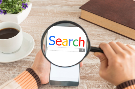 Search and modern lifestyle concept. Women hands Use the magnifying glass screen smart phone for search data on the desk.